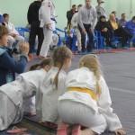 девочки-спортсменки наблюдают за борьбой в центре татами
